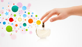 manos que rocían burbujas coloridas de la botella de perfume hermosa Fotos de archivo libres de regalías