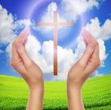 Manos que ruegan con la cruz en cielo - concepto de pascua Imágenes de archivo libres de regalías