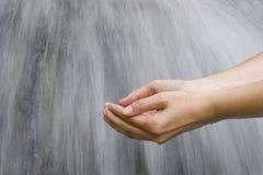 Manos que sacan el agua con pala Imágenes de archivo libres de regalías