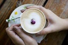Manos que se calientan contra un café Fotos de archivo libres de regalías