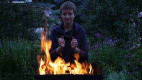 Manos que se calientan de la mujer cerca del fuego almacen de metraje de vídeo