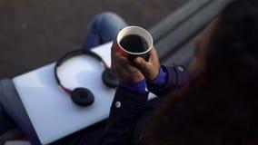 Manos que se calientan de la mujer, sosteniendo la taza con la bebida caliente fragante mientras que se sienta al aire libre Fotos de archivo