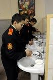 Manos que se lavan antes de comer en el comedor en el cuerpo del cadete de la policía Imagen de archivo