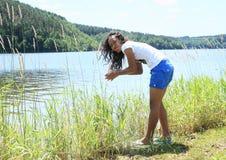 Manos que se lavan de la muchacha en el lago Fotos de archivo libres de regalías