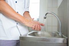 Manos que se lavan del cocinero hermoso en cocina comercial foto de archivo