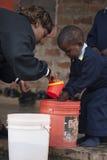 Manos que se lavan del niño en la escuela en África Imagen de archivo libre de regalías