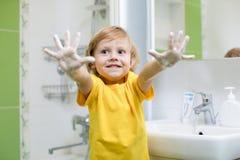 Manos que se lavan del niño y mostrar las palmas jabonosas Foto de archivo