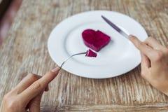 Manos que se preparan para comer el corazón en la placa Imagen de archivo