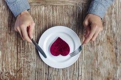 Manos que se preparan para comer el corazón en la placa Imagenes de archivo