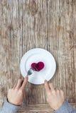 Manos que se preparan para comer el corazón en la placa Foto de archivo