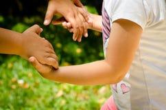 Manos que se unen a de la chica joven con su madre a jugar Imagen de archivo libre de regalías