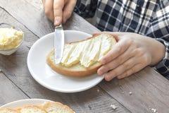 Manos que separan la mantequilla en el pan Imagen de archivo libre de regalías