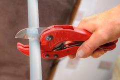 Manos que sondean con un cortador para los tubos plásticos imagenes de archivo