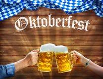 Manos que soportan las tazas de cerveza debajo de bandera bávara imágenes de archivo libres de regalías