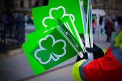 Manos que sostienen banderas verdes con el símbolo del trébol para la celebración del día del ` s de St Patrick Foto de archivo