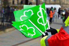 Manos que sostienen banderas verdes con el símbolo del trébol para la celebración del día del St Patricks Imágenes de archivo libres de regalías