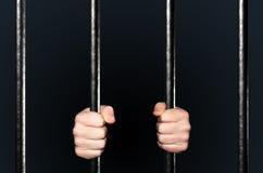 Manos que sostienen barras de la cárcel Fotografía de archivo libre de regalías