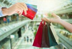 Manos que sostienen bolsos y tarjetas de crédito Fotos de archivo libres de regalías