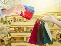 Manos que sostienen bolsos y tarjetas de crédito Fotos de archivo