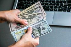 Manos que sostienen cientos y cincuenta billetes de banco del dólar