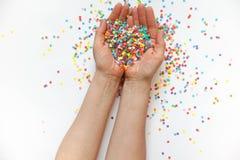 Manos que sostienen confeti festivo Fondo blanco Pequeños círculos Fotos de archivo