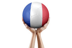 Manos que sostienen el balón de fútbol con la bandera de Francia Imágenes de archivo libres de regalías