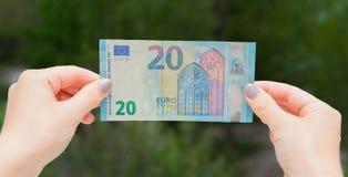 Manos que sostienen el billete de banco del euro 20 en el fondo verde Compruebe el euro para saber si hay autenticidad imágenes de archivo libres de regalías