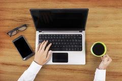 Manos que sostienen el café y que usan el ordenador portátil Foto de archivo libre de regalías