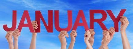 Manos que sostienen el cielo azul de enero de la palabra recta roja Imágenes de archivo libres de regalías