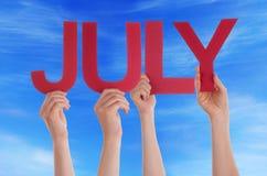 Manos que sostienen el cielo azul de julio de la palabra recta roja Fotografía de archivo