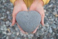 Manos que sostienen el corazón/la piedra en forma de corazón Imagenes de archivo