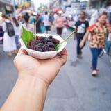 Manos que sostienen el cuenco de moras en Chiang Mai Walking Street Fotografía de archivo libre de regalías