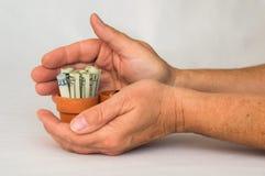 Manos que sostienen el dinero en un pote de la terracota Fotos de archivo libres de regalías