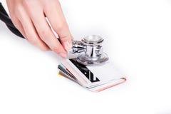 Manos que sostienen el estetoscopio en tarjetas de crédito como símbolo del coche del dinero Imágenes de archivo libres de regalías