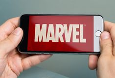Manos que sostienen el iPhone 6 de Apple con Logo Of Brand Marvel foto de archivo