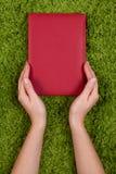 Manos que sostienen el libro rojo imagenes de archivo