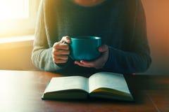 Manos que sostienen el libro y que leen con café Imagenes de archivo