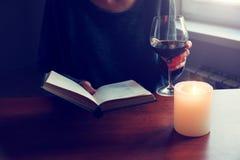 Manos que sostienen el libro y que leen con el vino Imágenes de archivo libres de regalías