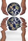 Manos que sostienen el planeta Fotos de archivo libres de regalías