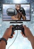 Manos que sostienen el regulador del juego con el combatiente del boxeador en la televisión Imagen de archivo