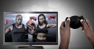 Manos que sostienen el regulador del juego con los combatientes del boxeo en la televisión Imágenes de archivo libres de regalías