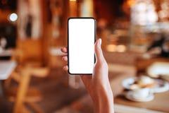 Manos que sostienen el smartphone blanco de la pantalla en fondo borroso imagen de archivo libre de regalías