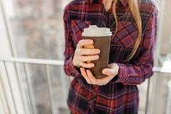Manos que sostienen el té de consumición de la muchacha de papel del café, primer, fotos de archivo