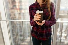 Manos que sostienen el té de consumición de la muchacha de papel del café, primer, imágenes de archivo libres de regalías