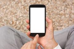 Manos que sostienen el teléfono elegante con la pantalla vacía en blanco blanca Foto de archivo