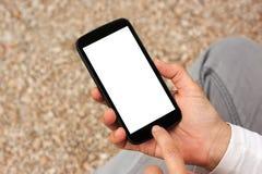 Manos que sostienen el teléfono elegante con la pantalla vacía en blanco blanca Fotografía de archivo libre de regalías