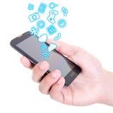 Manos que sostienen el teléfono elegante móvil con diversos usos y Imagenes de archivo
