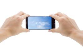 Manos que sostienen el teléfono elegante móvil con el cielo en pantalla Fotos de archivo
