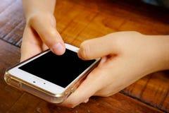 2 manos que sostienen el teléfono elegante móvil con la pantalla en blanco Foto de archivo libre de regalías