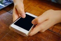 2 manos que sostienen el teléfono elegante móvil con la pantalla en blanco Fotografía de archivo libre de regalías